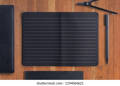 Blank black notebook and pen on wood background.Copy Space