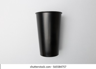 Blank black paper cup on the grey background