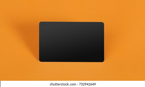 blank black plastic card on orange background