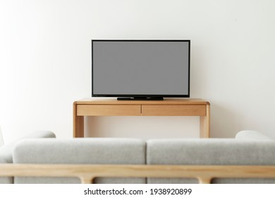 Blank black smart TV screen on a wooden table