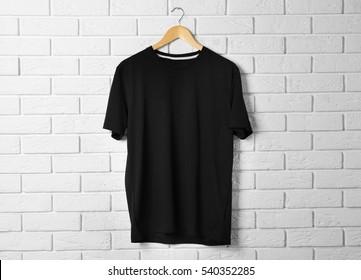 Blank black t-shirt against brick wall