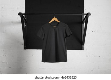 Blank black t-shirt presented on wooden hang on pullbar in home gym
