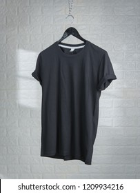 Blank Black T-Shirts Mock-up hanging against white brick wall,shadows from a window frame