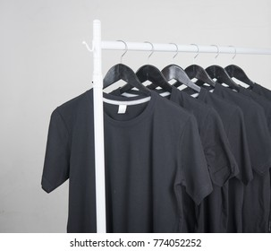Blank Black T-Shirts Mock-up on hangers on gray background
