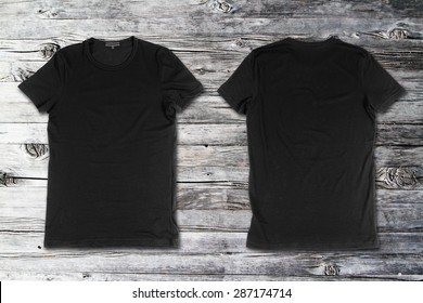 Blank black t-shirts on a wooden surface