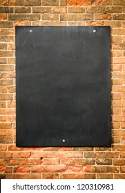 blank blackboard at a brick wall - nice background with space for text