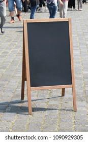 blank blackboard chalkboard advertising a-frame sign or customer stopper in pedestrian street