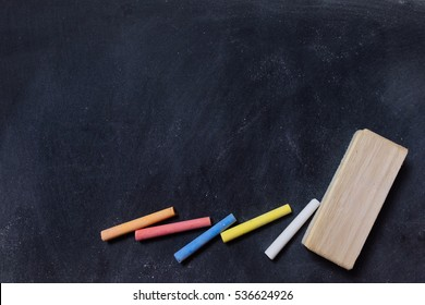 Blank blackboard with colored chalks and eraser. Horizontal composition.