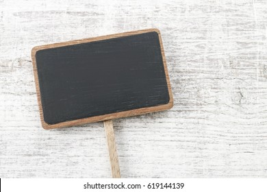Blank blackboard label isolated on a white wooden background, copy space.