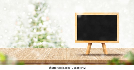 Blank blackboard menu on wood plank table top with abstract blur christmas tree red decor ball and snow fall background with bokeh light,Holiday backdrop,Mock up banner for display or montage of produ