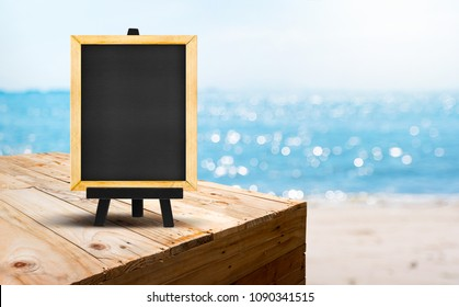 Blank blackboard on wood table food stand with blur sand beach and blue sea with bokeh light background.Template Mock up for summer vacation promotion sale