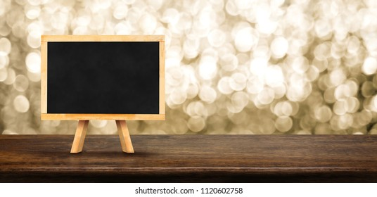 Blank blackboard on wood table with blur abstract sparkle gold background bokeh light,Mock up for display of product,Banner or header for advertise on online media,Holiday celebrate