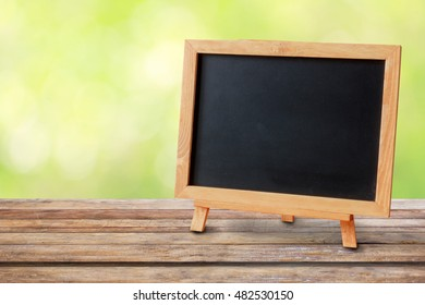 Blank blackboard on wooden table with garden bokeh for a catering or food background with a country outdoor theme,Template mock up for display of product