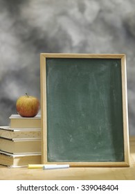blank blackboard resting on stack of books