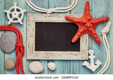 Blank blackboard with sea shells, rope, anchor and star fish on light wood, text space