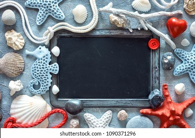 Blank blackboard with sea shells, stones, rope and star fish on textured light blue background, text space