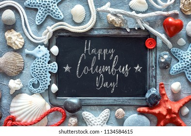 """Blank blackboard with sea shells, stones, rope and star fish on textured light blue background, text """"Happy Columbus Day"""""""