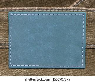 blank blue leather label on brown denim background