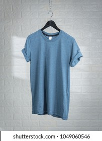 Blank Blue T-Shirts Mock-up hanging against white brick wall,shadows from a window frame