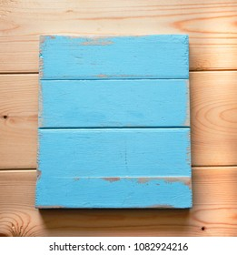 Blank board with peeling paint in pastel blue as a shabby chic, wooden background for design.