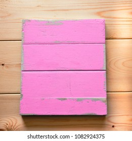 Blank board with peeling paint in pastel pink as a shabby chic, wooden background for design.