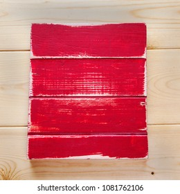 Blank board with red paint, wooden background for design.