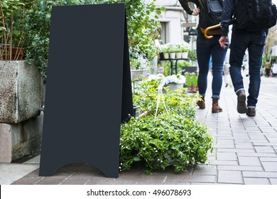 Blank Board stand mock up Black metal Signage Outdoor with people walking sidewalk Shop