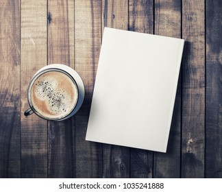 Blank book and coffee cup on vintage wood background. Responsive design template. Flat lay.