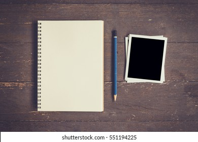 Blank Book open and photo frame on wood table with space.