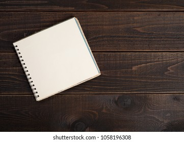 Blank book that is open and is laying on a rustic dark wood board table background with empty room or space for your copy, text, words or design.  A Horizontal photo and is flat layout shot from above