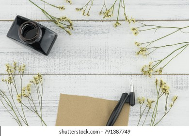 Blank brown card, oblique pen and bottle of ink decorated with yellow limonium caspia flowers on white wood background with copy space