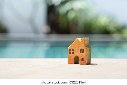 Blank brown card and wooden miniature house over blurred background