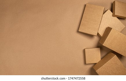 Blank brown cardboard boxes on craft paper background, top view with copy space, product package mock up