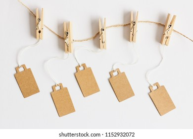 Blank brown cardboard price tags, sale tag, gift tag, address label, luggage label hanging on clothes wooden clips on white background. Mock up, copy space for text, top view