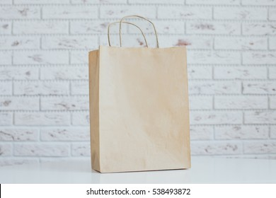 Blank brown craft paper bag design mockup. Mock-up of blank craft package, mockup of brown craft paper shopping bag with handles on the brick white background.
