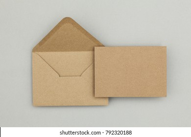 Blank brown kraft paper card and envelope on a grey background