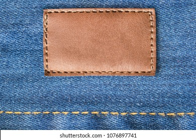 Blank brown leather label on blue denim background closeup