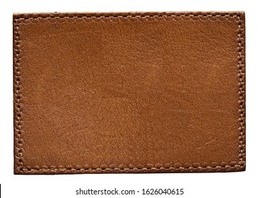Blank brown leather label on white background, macro close up. Leather patch with stitching
