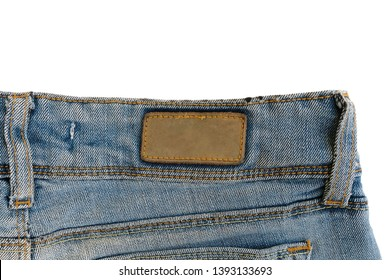 Blank brown leather label sewed on a blue jeans. Fragment of jeans trousers with brown patch
