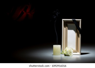 Blank brown mourning frame, with smoky candle and white rose, on dark background with red decoration