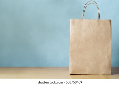 Blank brown paper carrier bag with handles for shopping, facing front on right side of a light wood veneer table with pale blue wall background providing copy space to left.