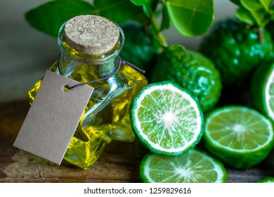 blank brown paper tag on bergamot orange citrus essential oil bottle with slices bergamot for hair beauty spa concept