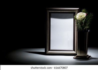 blank brown picture frame with white rose for mourning card
