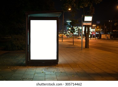 Blank bus stop advertising billboard in the city at night.