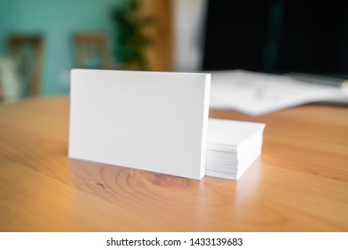 Blank business cards and laptop on wooden surface.