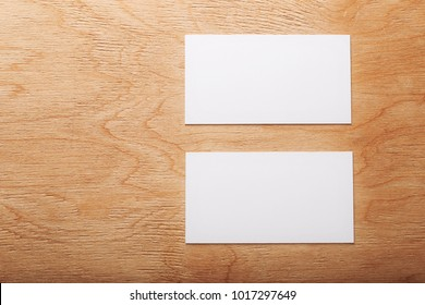 Blank business cards on wooden surface.