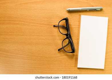 Blank business cards with pen and glasses on wooden office table