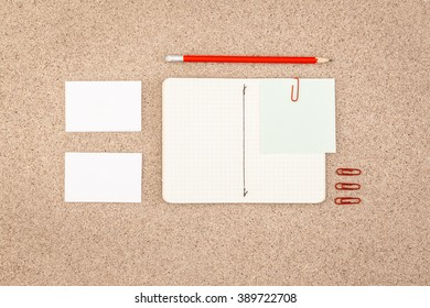 Blank business cards and scrapbook on a wooden table. View from above