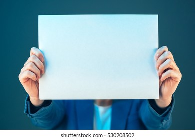 Blank business document paper covering businesswoman's face, copy space for text