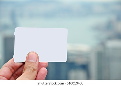 Blank business visit card, gift card, pass, ticket is being held by left hand with blurred city in a background. Copy space. Ready for adding card detail.